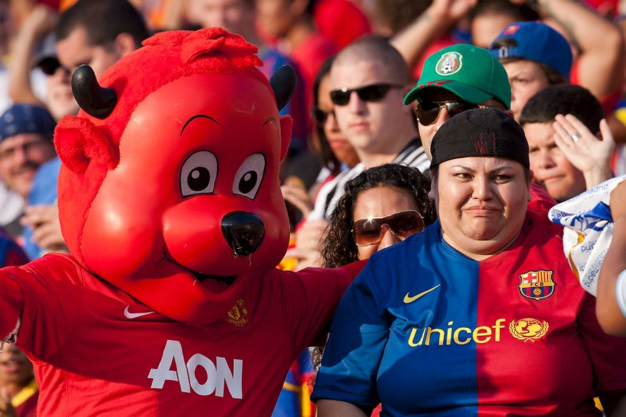 An FC Barcelona fan expresses her distaste while taking a picture with the Manchester United mascot during the 2011 Herbalife World Football Challenge match between Manchester United and FC Barcelona at FedEx Field in Landover, Md. on Saturday, July 30, 2011. (Pratik Shah/The Washington Times)