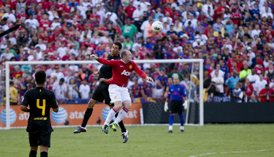 Manchester United forward Wayne Rooney wins a header against FC Barcelona midfielder Sergio Busquets during the 2011 Herbalife World Football Challenge match between Manchester United and FC Barcelona at FedEx Field in Landover, Md. on Saturday, July 30, 2011. (Pratik Shah/The Washington Times)