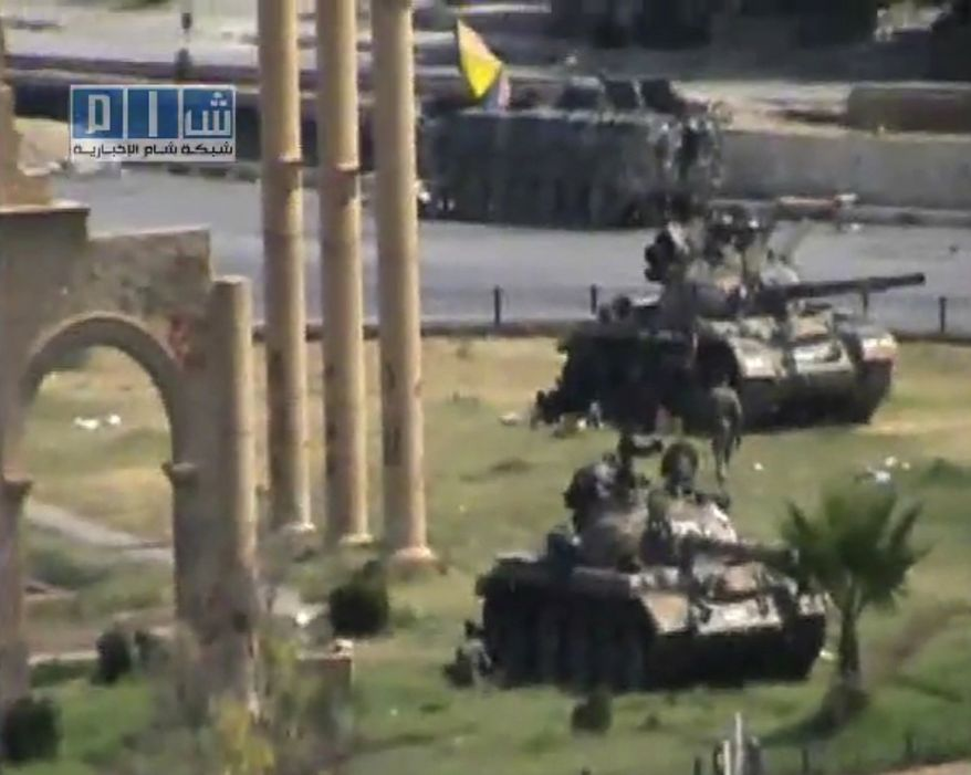 In this image made from amateur video released by the so-called Shams News Network, a loosely organized anti-Assad group and accessed via The Associated Press Television News on Monday, Aug. 1, 2011, military armored vehicles are seen in the central city of Hama, Syria. (AP Photo/APTN)