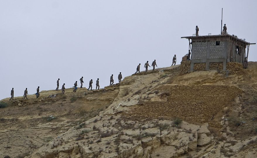 **FILE** Paramilitary troops move on hilltop to take positions on July 9, 2011, after security forces took control of a troubled area of Karachi, Pakistan. (Associated Press)