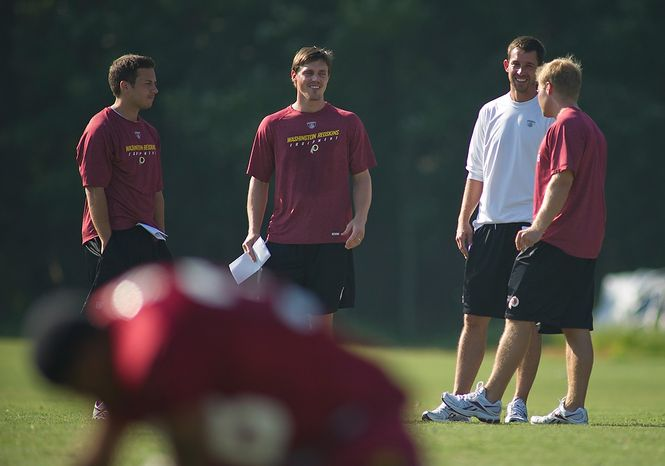 Washington Redskins Offense Coordinator Kyle Shanahan (second from right) chats with tight ends coach Sean McVay (right) and Coaching Assistant Richmond Flowers (second from left) during training camp at Redskins Park in Ashburn, Va., Tuesday, August 2, 2011. The man at far left is unidentified. (Rod Lamkey Jr./The Washington Times)