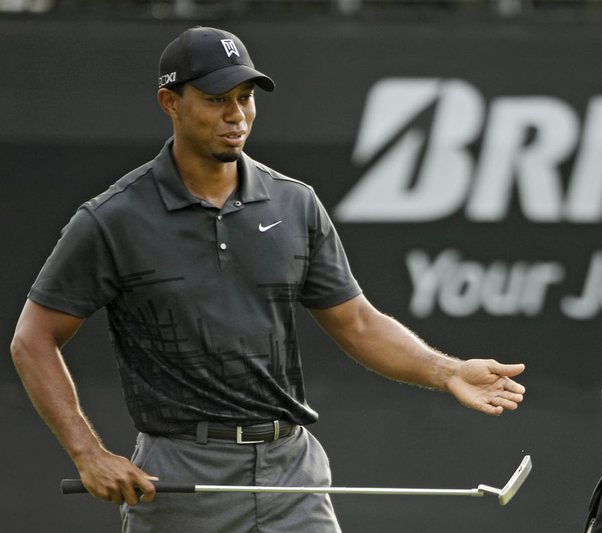 Tiger Woods watches his putt on the ninth green during practice for the Bridgestone Invitational golf tournament at Firestone Country Club in Akron, Ohio Tuesday, Aug. 2, 2011. (AP Photo/Mark Duncan)
