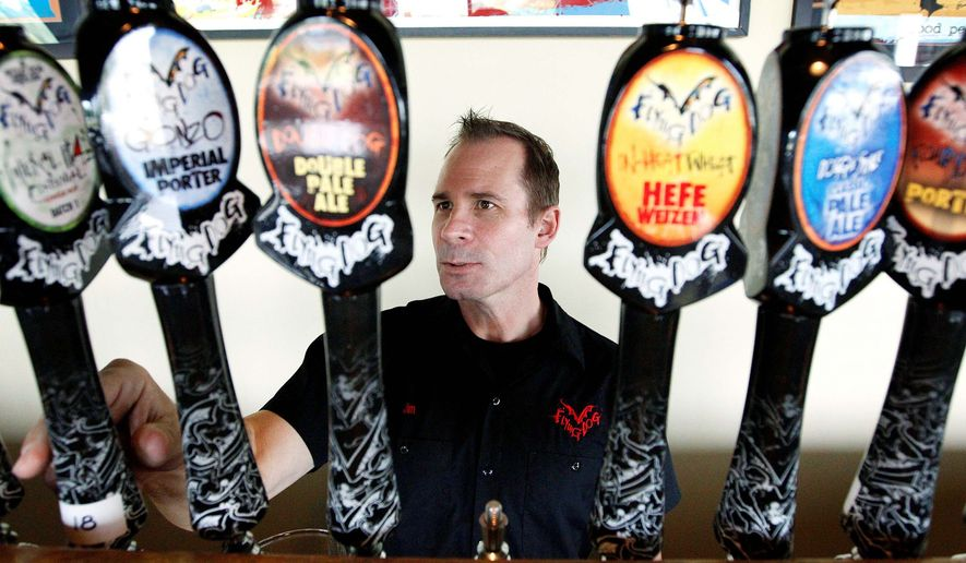 Jim Caruso, chief executive officer of Flying Dog Brewery, selects a beer to pour from a tap at the brewery's headquarters. **FILE**