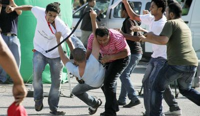 EMOTIONAL: Protesters clash outside the Cairo courthouse where ousted Egyptian President Hosni Mubarak's trial started Wednesday. The ailing ex-president arrived by helicopter and was wheeled in on a hospital gurney. (Associated Press)