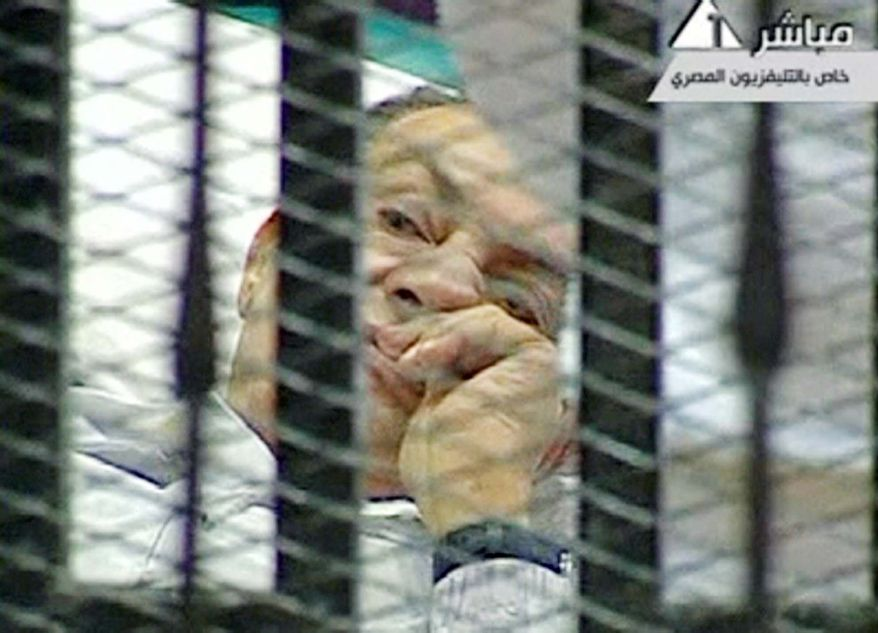 ON TRIAL: Former Egyptian President Hosni Mubarak lies on a hospital gurney in a cage of mesh and bars in a Cairo courtroom Wednesday as his trial begins. (Egyptian State TV via Associated Press)