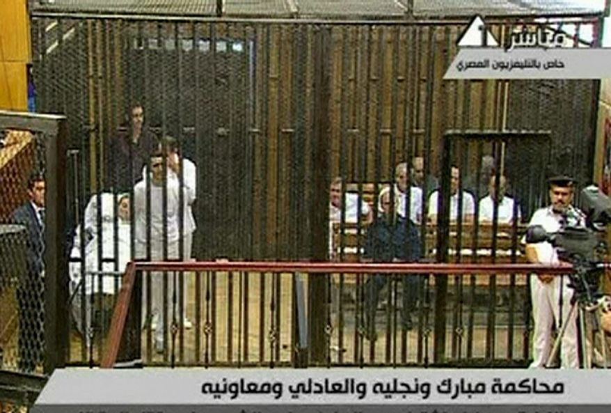 "Ousted Egyptian President Hosni Mubarak lies on a hospital gurney (left) inside a cage in a courtroom in Cairo as other defendants sit on the right. Mr. Mubarak, his two sons and seven other defendants are charged with ""premeditated murder"" of hundreds of protesters. (Egyptian State Television via Associated Press)"