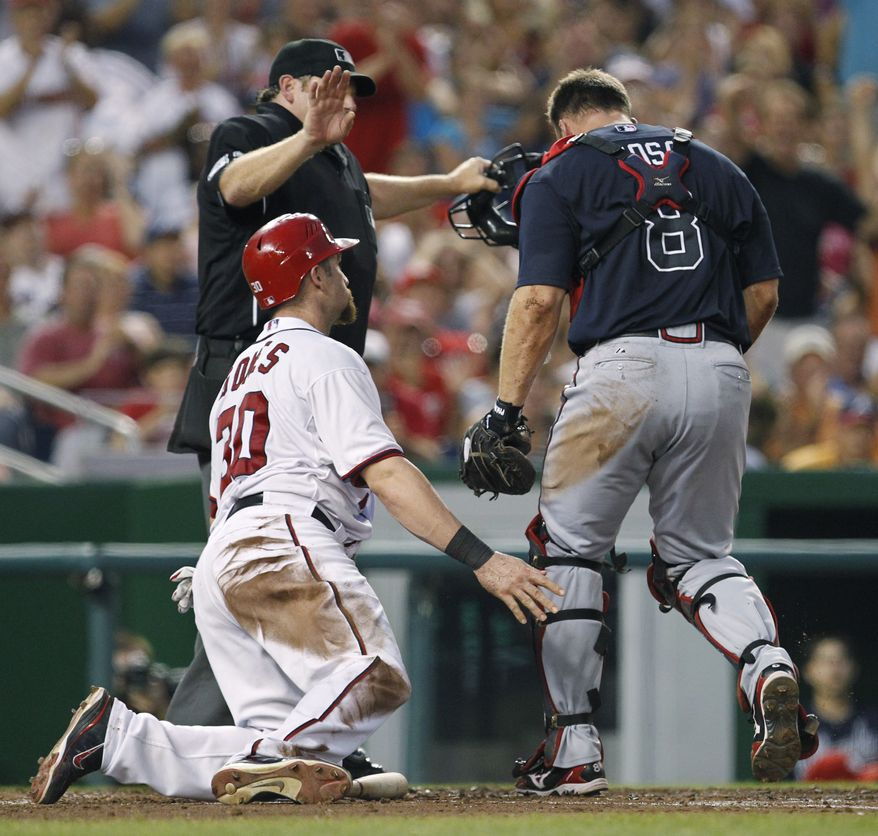 Atlanta Braves catcher David Ross makes an appeal to home base umpire Paul Schrieber after Washington Nationals left fielder Jonny Gomes was called safe during the fourth inning Tuesday. The Nationals won 9-3. (AP Photo/Manuel Balce Ceneta)