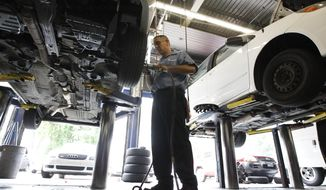 **FILE** In this photo from July 6, 2011, technician Chris Sparacino works on a costumers car at a Pep Boys Auto retail and service location in Philadelphia. (Associated Press)