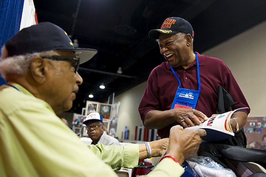 """From left, original members of the Tuskegee Airmen George W. Porter, from Sacramento, Calif., and Harry Quinton, from Williamsburg, Va., share a laugh as they look through a commemorative journal of Tuskegee Airman history, on the first day of the 40th Annual Tuskegee Airmen National Convention, at the Gaylord Hotel and Convention Center, in National Harbor, Md., Wednesday, Aug. 3, 2011. Both Porter and Quinton served as mechanics and flight engineers in the Tuskegee Airmen. """"It's wonderful to come back and see everyone,"""" said Porter. """"We didn't even realize we were stationed at the same base together until we met here."""" The two were both stationed at Godman Field near Fort Knox in Louisville, Ky. (Drew Angerer/The Washington Times)"""