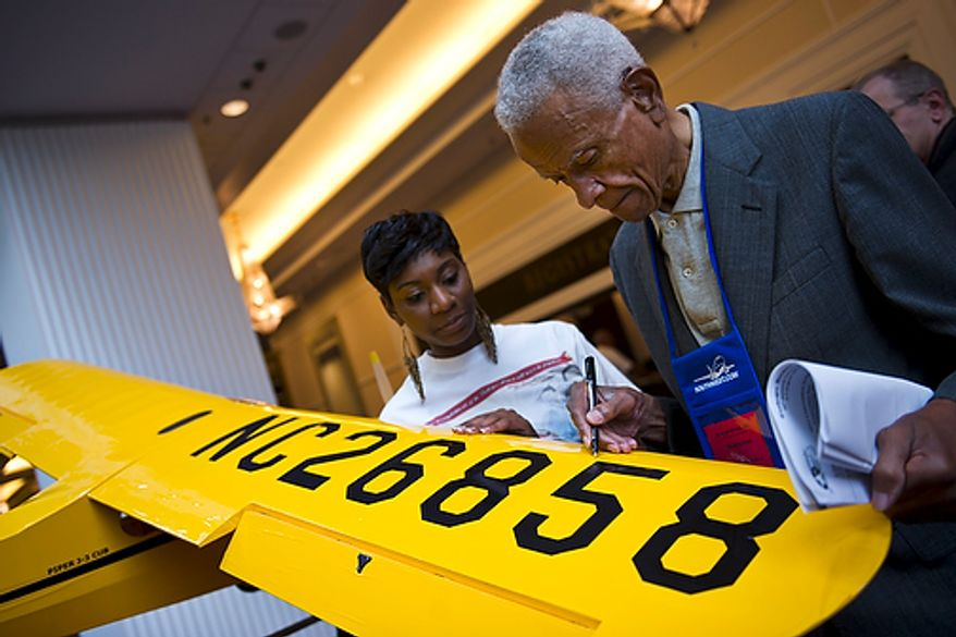 """Dr. Donald Jackson, a bomber pilot and original Tuskegee Airman, signs a model of a Piper J-3 Cub Plane, often used for training and a popular light aircraft of its time, on the first day of the 40th Annual Tuskegee Airmen National Convention, at the Gaylord Hotel and Convention Center, in National Harbor, Md., Wednesday, Aug. 3, 2011. At left is convention volunteer Linze Greene, from Dallas. Her father and great uncle were both original Tuskegee Airmen. """"You see these other guys here and it just does something wonderful for your human  psyche,"""" said Dr. Jackson, who is making his 6th trip to the convention this year. (Drew Angerer/The Washington Times)"""