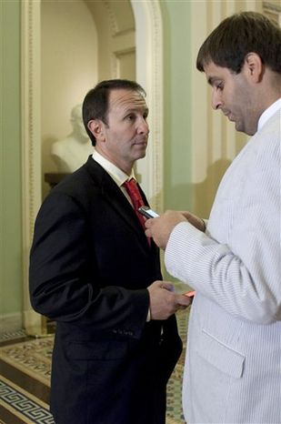 **FILE** Rep. Jeff Landry (left), Louisiana Republican, talks with an aide outside of the Senate Chamber on Capitol Hill on July 29, 2011. (Associated Press)