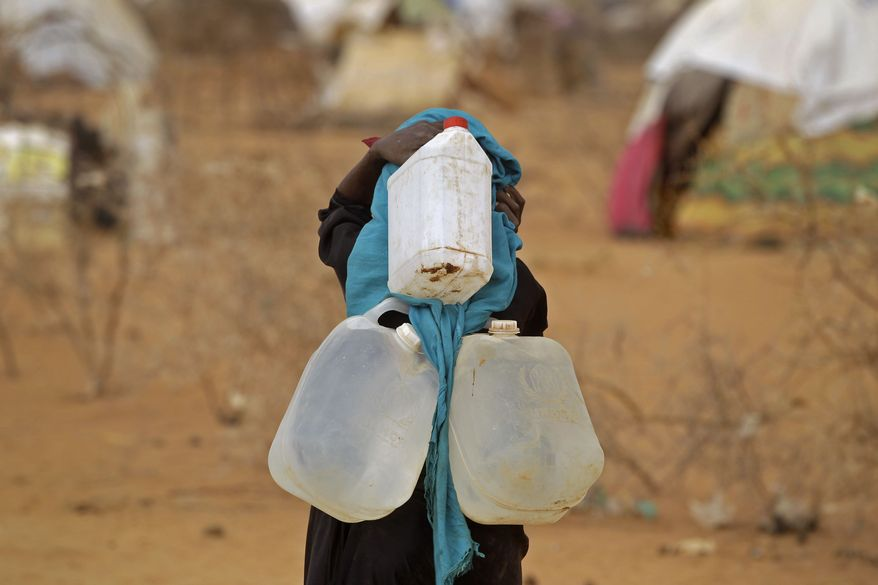 A woman carries three water containers on her back to her home on Aug. 4, 2011, at a refugee camp in Dadaab, Kenya. The camp, designed for 90,000 people, now houses about 440,000 refugees, almost all from war-ravaged Somalia. (Associated Press)