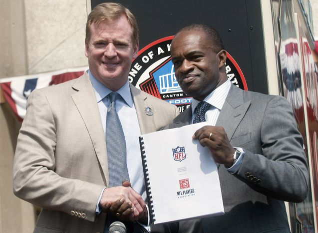 NFL Comissioner Roger Goodell and NFLPA Executive Director DeMaurice Smith shake hands after signing their collective bargaining agreement at the Pro Football Hall of Fame in Canton, Ohio on Friday. (AP Photo/Phil Long)