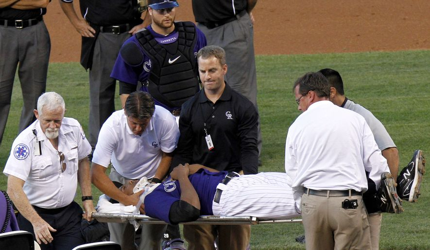 Colorado Rockies starting pitcher Juan Nicasio is taken off the field by medical personnel after Washington Nationals' Ian Desmond hit him in the head with a line drive during the second inning Friday. (AP Photo/Barry Gutierrez)