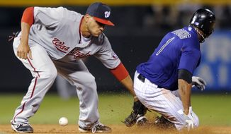 Colorado Rockies' Eric Young Jr. steals second as Washington Nationals shortstop Ian Desmond bobbles the ball during the seventh inning on Thursday. The Nats lost 6-3. (AP Photo/ Jack Dempsey)