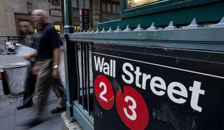 **FILE** Pedestrians walk past a Wall Street sign near the New York Stock Exchange. (Associated Press)