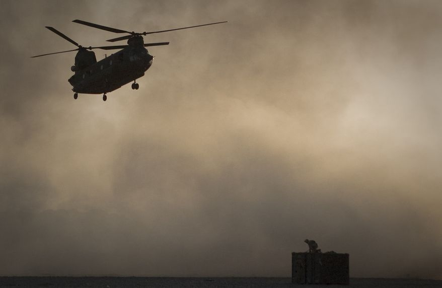 ** FILE **  A U.S. Marine, perched on a container, tries to take shelter from the dust as a Chinook helicopter arrives to pick up supplies at Forward Operating Base Edi in Helmand province in southern Afghanistan on Thursday, June 9, 2011. (AP Photo/Anja Niedringhaus)