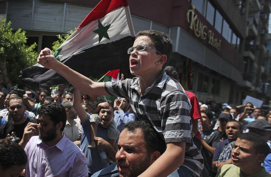 An Egyptian boy sits on the shoulders of a man during a protest against the Syrian regime, in Cairo, Egypt, Friday, Aug. 5, 2011.  (AP Photo/Tara Todras-Whitehill)