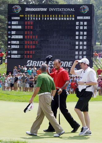 ASSOCIATED PRESS Tiger Woods (center) walks off the 18th green at Firestone Country Club after finishing his first tournament since the Masters.