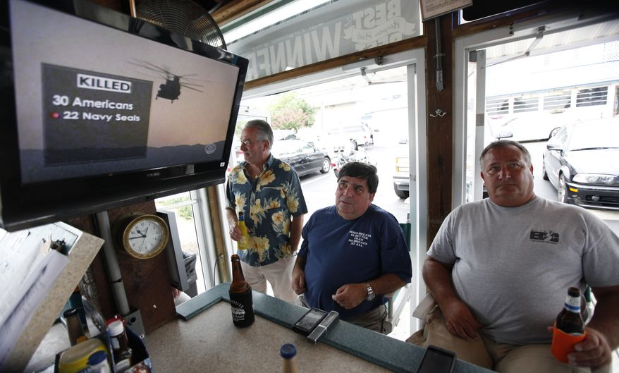 Virginia Beach residents Tom Hall (left) and Mark Janik (center) watch the news about the Navy SEAL Team 6 helicopter crash on Saturday, Aug. 6, 2011, in Virginia Beach, the headquarters of the elite Navy group, whose members captured Osama bin Laden. (AP Photo/Steve Helber)