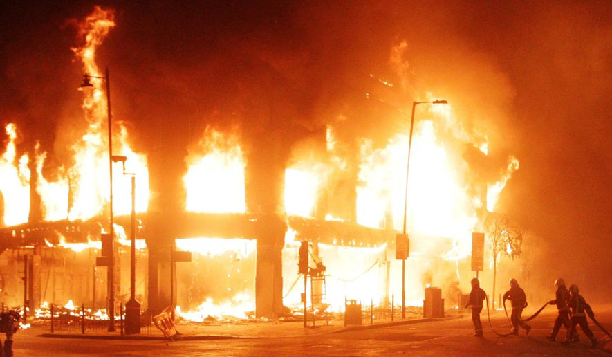 Firefighters attempt to put out a blaze in a building in the Tottenham section of north London on Sunday, Aug. 7, 2011, after a demonstration against the death of a local man turned violent and cars and shops were set ablaze. (AP Photo/PA, Lewis Whyld)