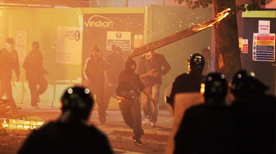"""A rioter throws a burning wooden plank at police in Tottenham, north London Sunday Aug. 7, 2011, after members of a community, where a young man was shot dead by police, took to the streets to demand """"justice."""" (AP Photo/PA, Lewis Whyld)"""