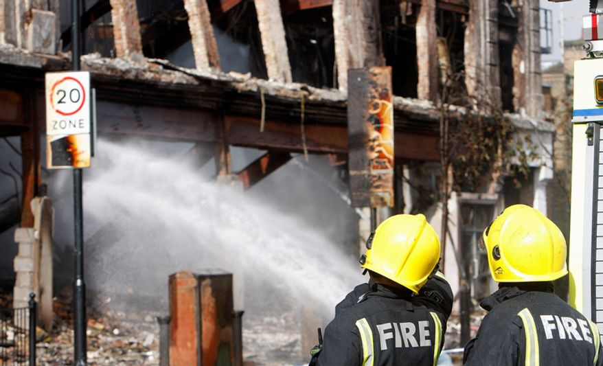 Firefighters look at a burned-out building in Tottenham, north London, still being damped down after a demonstration against the death of a local man turned violent and cars and shops were set ablaze.  (AP Photo/Akira Suemori)