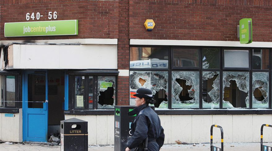 A police officer walks past a Jobcentre Plus, where windows have been smashed, in Tottenham, after a demonstration against the death of a local man turned violent and cars and shops were set ablaze.  (AP Photo/Akira Suemori)