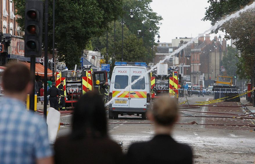 People look down High Street in Tottenham, north London, Sunday, Aug. 7, 2011 after a demonstration against the death of a local man turned violent and cars and shops were set ablaze. (AP Photo/Akira Suemori)