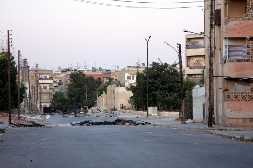 In this photo taken during a government organized tour, a road is blocked in the central city of Hama, Syria, on Aug. 7, 2011. (Associated Press)