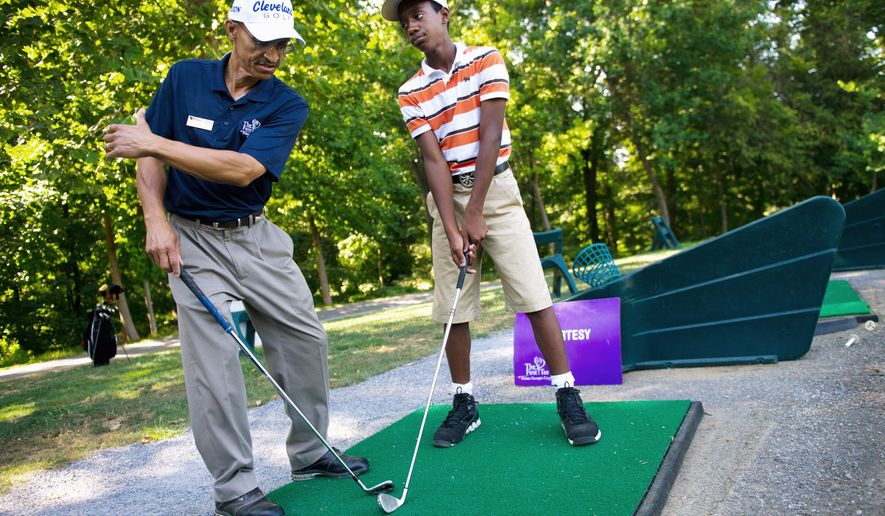 """Nicholas Babb, 12, of Mitchellville, right, gets tips on his swing on the range from Ed Artis, Executive Director of the First Tee program of Prince George's County, at Enterprise Golf Course, in Mitcheville, Md., Tuesday, July 26, 2011. Artis has been running the program in the county for 10 years. """"Using the platform of golf, we run a character development program for young kids,"""" said Artis. """"We want them to be good golfers, but more importantly we want them to make wise choices in life."""" Over 350 kids are enrolled in the First Tee program at Enterprise, with each student coming for an hour per week. (Drew Angerer/The Washington Times)"""