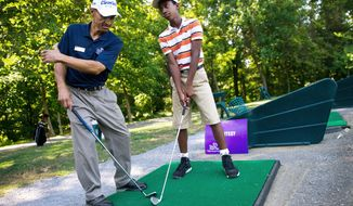 "Nicholas Babb, 12, of Mitchellville, right, gets tips on his swing on the range from Ed Artis, Executive Director of the First Tee program of Prince George's County, at Enterprise Golf Course, in Mitcheville, Md., Tuesday, July 26, 2011. Artis has been running the program in the county for 10 years. ""Using the platform of golf, we run a character development program for young kids,"" said Artis. ""We want them to be good golfers, but more importantly we want them to make wise choices in life."" Over 350 kids are enrolled in the First Tee program at Enterprise, with each student coming for an hour per week. (Drew Angerer/The Washington Times)"