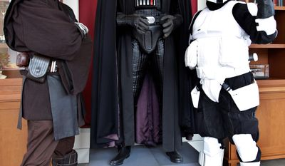 """** FILE ** """"Star Wars"""" fans Matt Tolosa (left), dressed as Anakin Skywalker, and his brother Dale, dressed as a Stormtrooper, pose with a Darth Vader mannequin at the Lucasfilm Ltd. headquarters in San Francisco.(Associated Press)"""