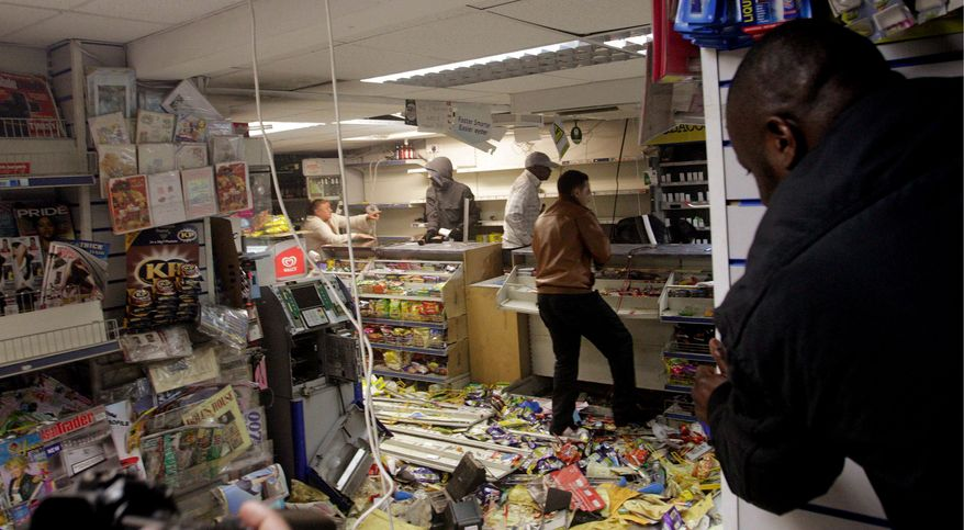 ASSOCIATED PRESS PHOTOGRAPHS  People loot a shop in the east London borough of Hackney on Monday. Rioting in London continued for a third day, spreading throughout the city after a peaceful protest Saturday turned violent. More than 200 people have been arrested, and 35 police officers have been injured. British police officers arrest a man (below) as rioters gathered in Croydon, south London, on Monday.