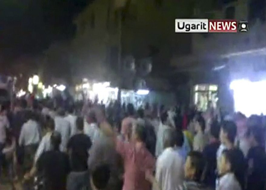 In this image made from amateur video released by Ugarit News and accessed via The Associated Press Television News on Monday, Aug. 8, 2011, show protestors on the street in Deir el-Zour on Sunday Aug. 7, 2011. The besieged Syrian city of Deir el-Zour came under fresh artillery fire early Monday as a deadly military assault left President Bashar Assad's regime increasingly isolated, with Arab nations forcefully joining the international chorus of condemnation for the first time. The renewed violence in the eastern city of Deir el-Zour comes a day after at least 42 people were killed there in an intensifying government crackdown on protesters. (AP Photo/Ugarit News via APTN)