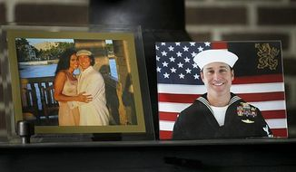 Photos of Navy SEAL Chris Campbell sit on the wood burning stove of his parents, Diane and Larry Campbell, Monday morning Aug. 8, 2011, in Jacksonville, N.C. On the left is a picture Chris with his wife Angelina taken approximately 3 yrs ago, and on the right is a picture of Campbell in his Navy uniform taken approximately 5 months ago. Campbell, 36, was one of 22 SEALs killed Saturday, Aug. 6, 2011, along with eight other U.S. troops and eight Afghans when their helicopter was brought down in Afghanistan, his family told The Daily News of Jacksonville. (AP Photo/The Jacksonville Daily News, John Althouse)