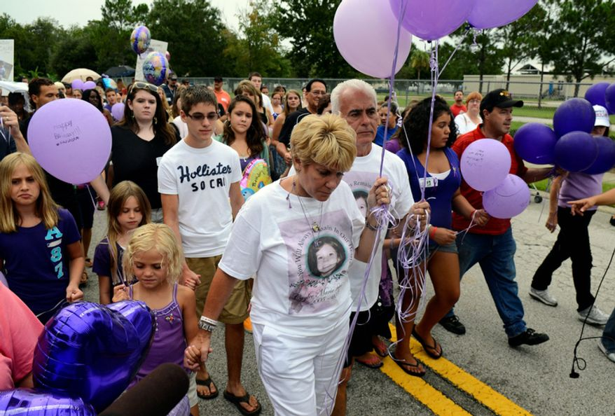 Cindy Anthony, center, and George Anthony, to her left, walk with well-wishers as part of a memorial ceremony near the site where the body of their granddaughter Caylee Anthony was found on what would have been her sixth birthday in Orlando, Fla., Tuesday, Aug. 9, 2011. Their daughter Casey Anthony was acquitted of the most serious charges related to the death of Casey's daughter, Caylee Anthony. (AP Photo/Phelan M. Ebenhack)