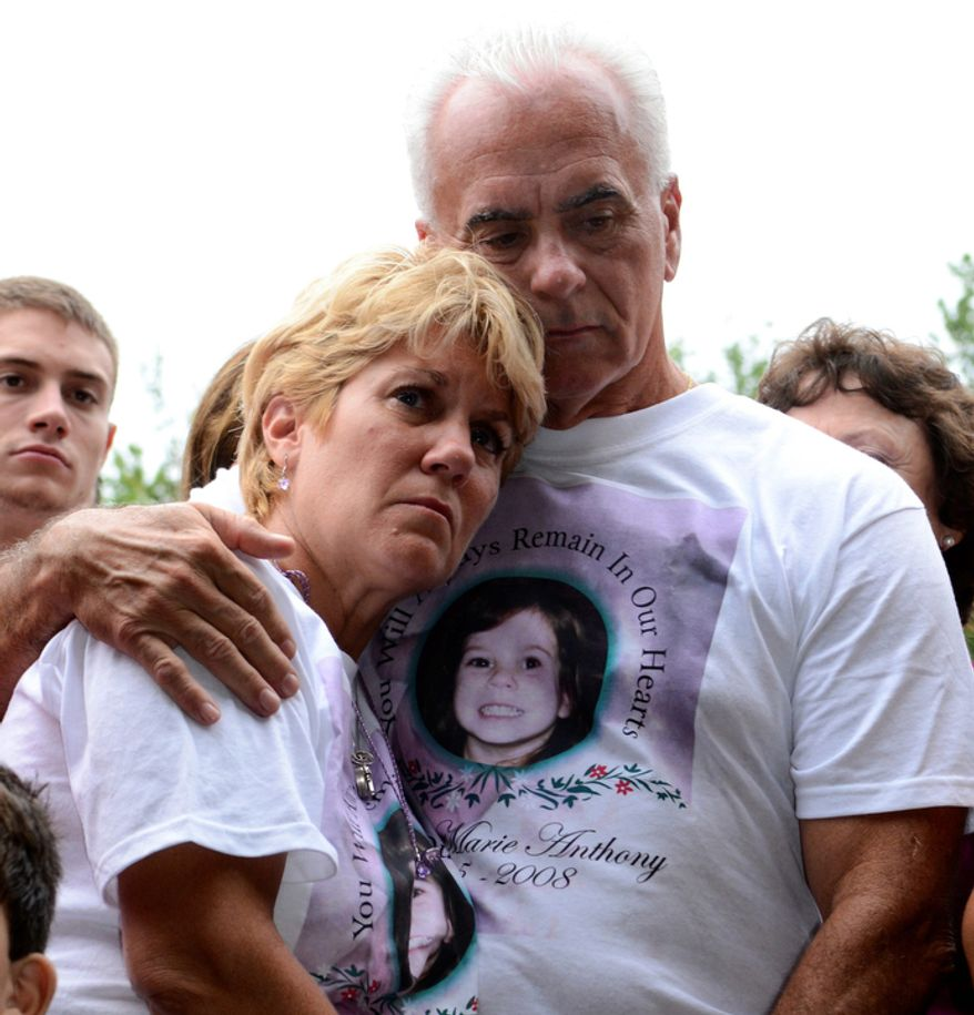 Cindy Anthony is comforted by George Anthony, right, during a memorial ceremony at the site where the body of their granddaughter Caylee Anthony was found on what would have been her sixth birthday in Orlando, Fla., Tuesday, Aug. 9, 2011. Their daughter Casey Anthony was acquitted of the most serious charges related to the death of her daughter Caylee Anthony. (AP Photo/Phelan M. Ebenhack)