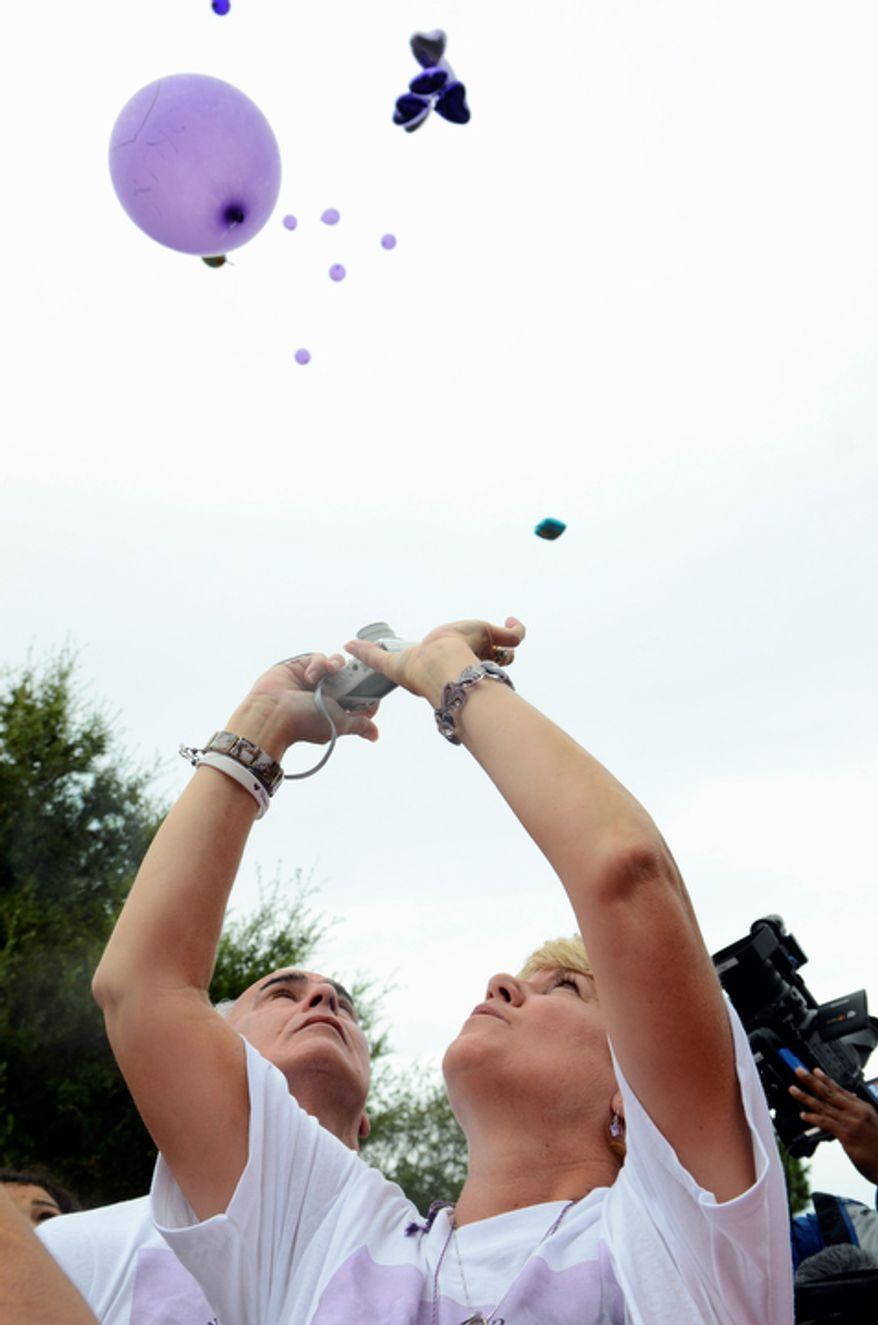 George Anthony, left, and Cindy Anthony watch as balloons are released as part of a memorial ceremony near the site where the body of their granddaughter Caylee Anthony was found on what would have been her sixth birthday in Orlando, Fla., Tuesday, Aug. 9, 2011. Their daughter Casey Anthony was acquitted of the most serious charges related to the death of Casey's daughter Caylee Anthony. (AP Photo/Phelan M. Ebenhack)