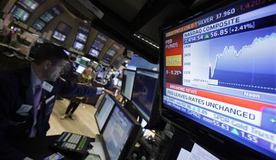 A television screen at the post of specialist Stephen Ruiz (left) displays the decision of the Federal Reserve on the floor of the New York Stock Exchange on Aug. 9, 2011. The Federal Reserve said Tuesday that it will likely keep interest rates at record lows for the next two years after acknowledging that the economy is weaker than it had thought and faces increasing risks. (Associated Press)