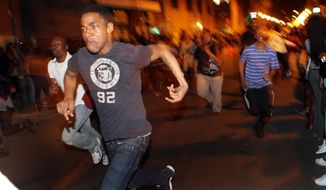 **FILE** In this photo from March 20, 2010, young people run down South Street in Philadelphia during a flash mob incident that involved thousands. (Associated Press/The Philadelphia Inquirer)