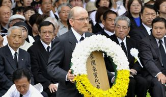 James P. Zumwalt, charge d'affaires at the U.S. Embassy in Tokyo, carries a wreath to an altar set up in Nagasaki Peace Park in Nagasaki, Japan, on Tuesday, Aug. 9, 2011, at the annual memorial to mark the 66th anniversary of the dropping of an atomic bomb on the city. (AP Photo/Kyodo News)
