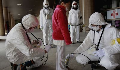 **FILE** In this photo from March 24, 2011, a young evacuee is screened at a shelter for leaked radiation from the damaged Fukushima nuclear plant in Fukushima, Fukushima prefecture, Japan. (Associated Press)