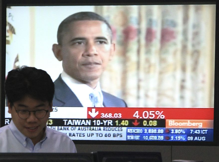 A currency trader works in front of a TV showing U.S. President Barack Obama at the Korea Exchange Bank headquarters in Seoul, South Korea, Tuesday, Aug. 9, 2011. Asian equity markets were sharply down early Tuesday as investors fearing a possible global economic slowdown continued to flee stocks. (AP Photo/Ahn Young-joon)
