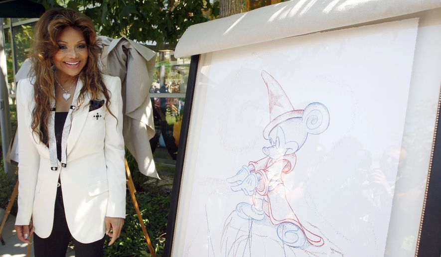 La Toya Jackson smiles in front of one of 13 original pieces of art by pop icon Michael Jackson that were donated Monday, Aug. 8, 2011, to the Children's Hospital in Los Angeles. (AP Photo/Nick Ut)