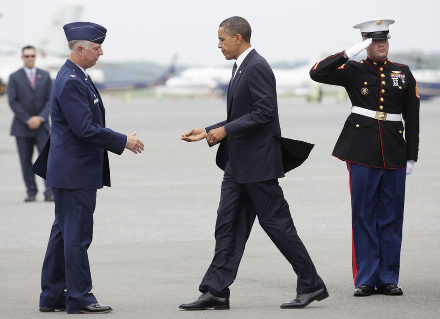 Col. Mark Camerer (left), commander of the 436th Airlift Wing at Dover Air Force Base in Delaware, greets President Obama on Tuesday, Aug. 9, 2011. Mr. Obama was expected to meet privately with families of 30 Americans killed over the weekend in an International Security Assistance Force helicopter crash in eastern Afghanistan while supporting Operation Enduring Freedom. (AP Photo/Carolyn Kaster)