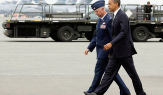 President Obama walks with Col. Mark Camerer, the 436th Airlift Wing Commander, upon the president's arrival at Dover Air Force Base in Dover, Del., on Aug. 9, 2011. (Associated Press)