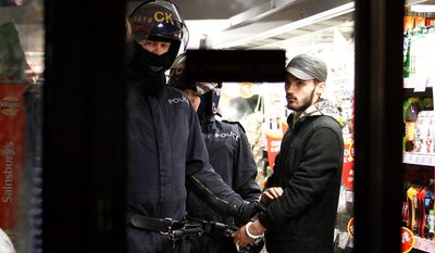 A riot policeman holds a looter in a Sainsbury's supermarket on Deansgate during civil disturbances in Manchester, England.  (AP Photo/Jon Super).