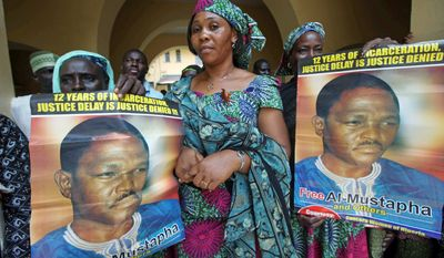 ASSOCIATED PRESS PHOTOGRAPHS Women display posters in support of Nigeria's former chief security officer, Maj. Hamza Al-Mustapha (leaving court Monday, below center), at the federal high court in Lagos. After nearly 14 years in prison, Maj. Al-Mustapha is facing trial on charges of orchestrating the killing of a political rival's wife, reopening old wounds from an era of terror in Nigeria.
