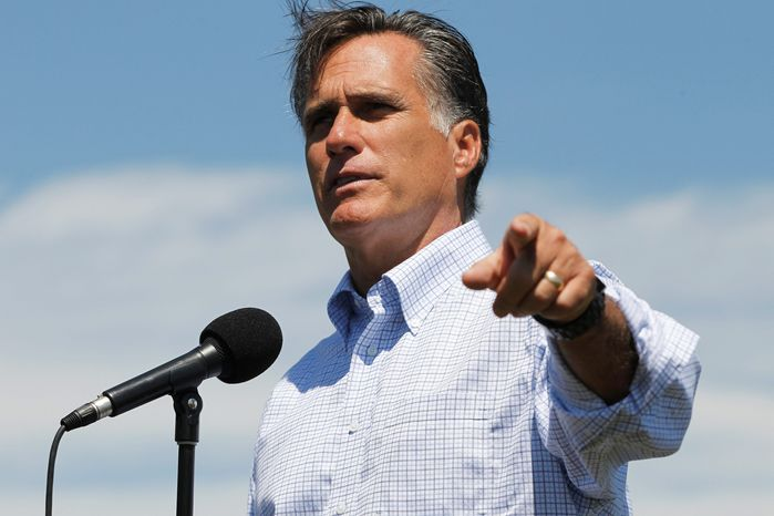 Former Massachusetts Gov. Mitt Romney answers reporters' questions after he talked about the economy at Vermeer Corporation in Pella, Iowa, on Wednesday. He'll be participating in a debate with other Republican presidential candidates on Thursday. (Associated Press)